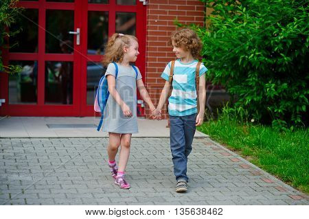 Boy and girl go to school having joined hands. Warm September day. Good mood. School students about something talk.