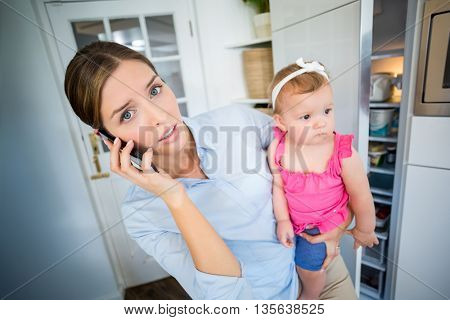 Close-up of tensed woman talking on mobile phone while carrying baby girl at home