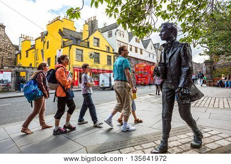 Edinburgh Scotland - July 28 2012: Royal Mile Canongate tourist walking near the statue of the poet Robert Fergussont.