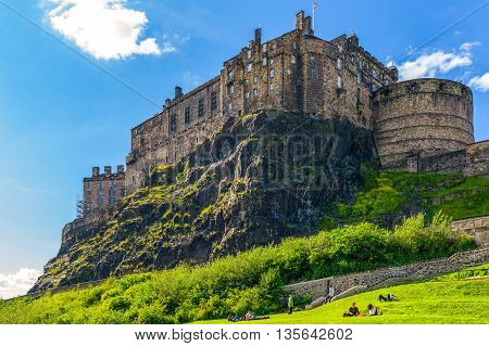 Edinburgh Scotland - June 19 2012: The Castle seen from the Grassmarket area with joung people sunbathing.