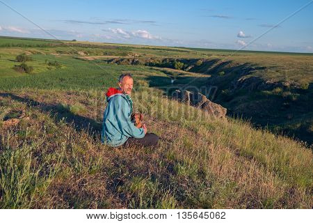 Dreaming hiker man sits with a dog in the prairie looking into the distance and enjoying life. Sunset in a prairie desert. Azov steppes Ukraine.
