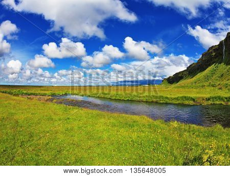Iceland in July. Green fields and streams near the giant ice plateau