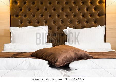 Luxury queen-size bed with a brown upholstered headboard and matching throw rug and cushions over the duvet in a home hotel or bed and breakfast