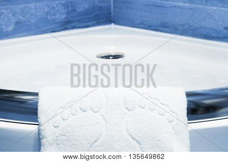 Cute white bathmat with footprints hanging over the lip of a corner shower cubicle with blue tiles in a low angle view
