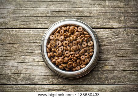 Dry kibble dog food in bowl on old wooden table. Top view.