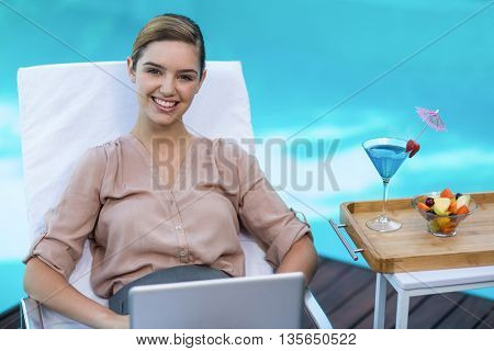 Portrait of businesswoman relaxing on sunlounger with laptop near pool