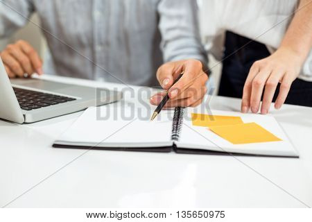 Midsection of male and female collegues discussing at desk in office