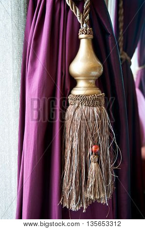 Elegantly draped silk curtain with golden tassles