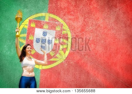 Front view of sportswoman raising a cup against digitally generated portugese national flag
