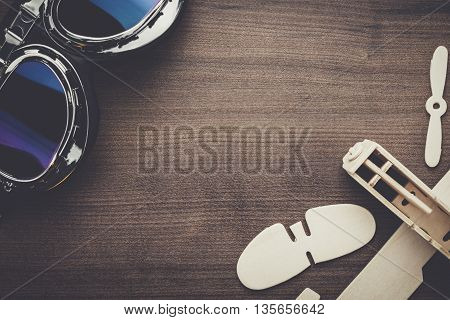 retro pilot glasses and handmade airplane on brown wooden table