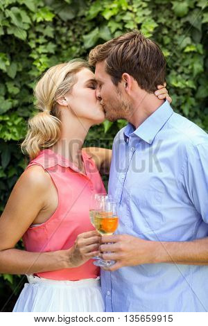 Happy couple kissing while toasting wineglasses at front yard