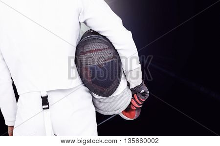 Rear view of swordsman holding fencing mask and sword against view of lights