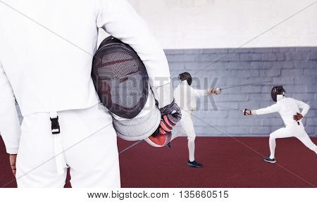 Rear view of swordsman holding fencing mask and sword against gym
