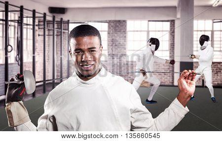 Portrait of swordsman standing with sword against gym