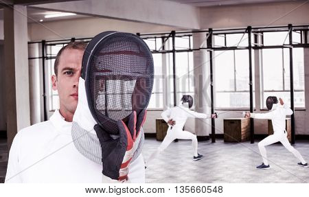 Swordsman holding fencing mask against interior view of a gym