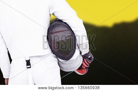 Rear view of swordsman holding fencing mask and sword against blurred mountains