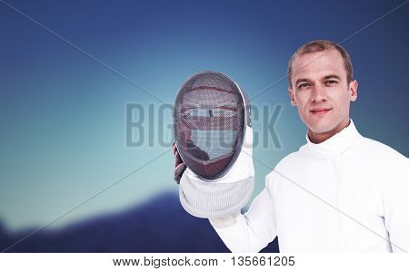 Swordsman holding fencing mask against dark blue green background