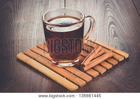 teacup with hot tea and cinnamon sticks on the table