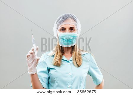 Nurse with protective mask and hair net is holding injection.