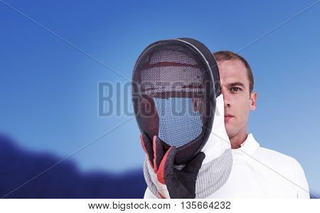 Swordsman holding fencing mask against scenic view of blue sky