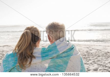 Rear view of happy mature couple looking at sunset at the beach. Back view of loving senior couple embracing at beach wrapped in towel. Retired couple in love relaxing at seaside.