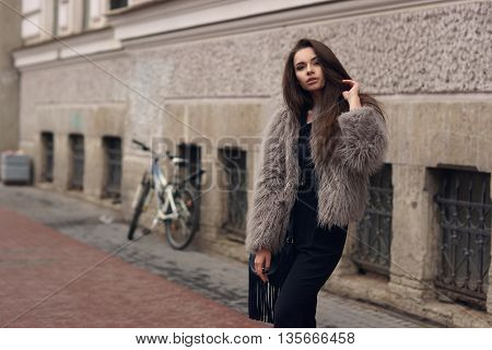Fashion style portrait of young beautiful elegant woman in black dress and gray fur coat walking at city street