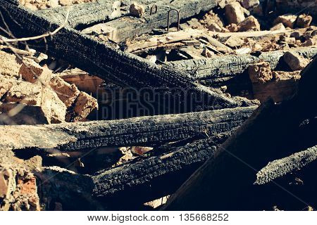 Many charred black logs on background of ruins
