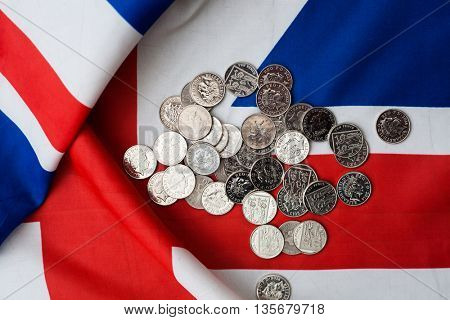Shiny coins on Union Jack flags - British pound fell sharply after referendum