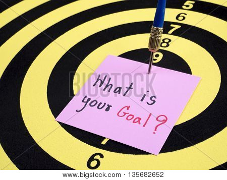 Handwriting What is your goal on notepaper with dart arrow and dart board. (Business concept)