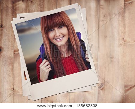 Smiling hipster woman with a travel bag taking selfie against wooden planks