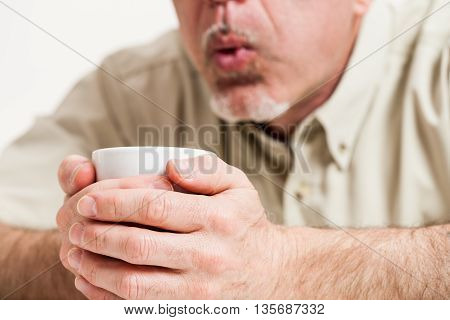 Cropped Head And Shoulders Of Man Blowing Into Cup