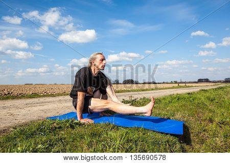 on an sunny day this man enjoys eka hasta bhujasana yoga in nature