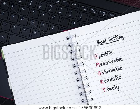 Handwriting SMART Goal on blank notebook with laptop keyboard