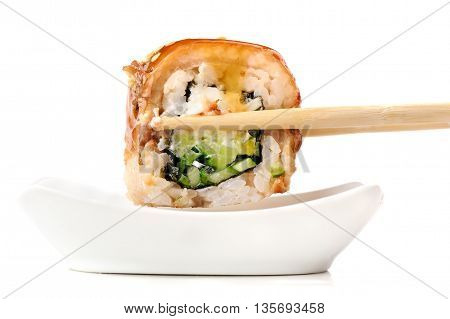 Sushi rolls with cream cheese nori and cucumber covered with eel and caramel sauce in chopsticks deeped in soy sauce isolated closeup