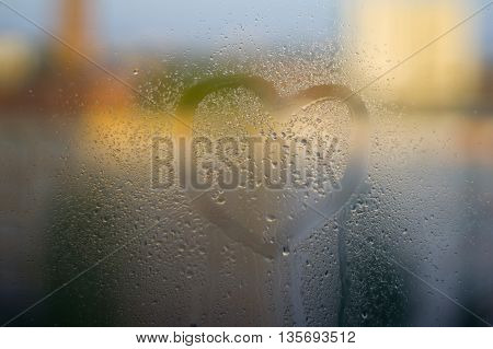 Heart painted on glass. The glass is fogged up and there are many drops on it