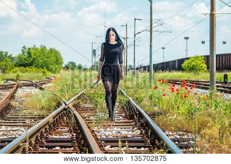 Young beautiful girl in black dress and nylons walking down rail tracks, cargo wagons and poppies in background