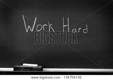 Chalkboard with chalk eraser marks in white chalk Work Hard Sign