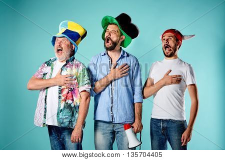 The three football fans singing the national anthem over blue background