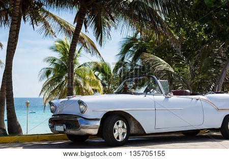 Beautiful white cabriolet vintage car before the beach in Varadero Cuba