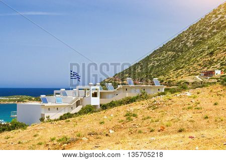 Modern Greek architecture - new white building in constructivist style stands on shore of Cretan sea on roof mounted solar panels with hot water heaters on flagpole the flag of Greece. Resort village Bali Rethymno Crete Greece