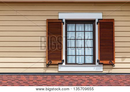 Window with brown shutters on the wooden wall of the building.
