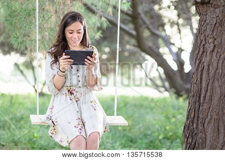 Smiling Woman with Tablet on a Swing in a Park