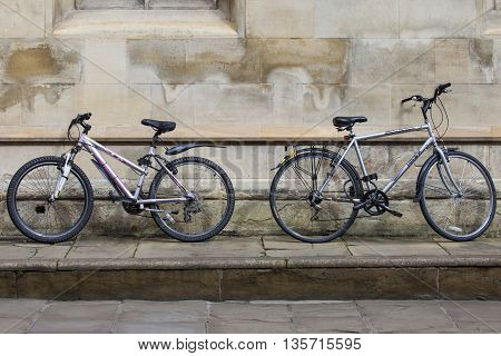 CAMBRIDGE UK - APRIL 8TH 2016: Two bicycles propped up against a wall in the university city of Cambridge in the UK on 8th April 2016. Bicycles are the quickest and cheapest mode of transport in and around the town.