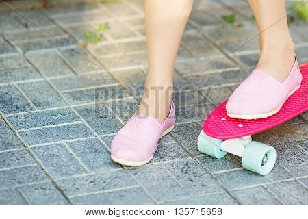 Girl Standing On A Pink Skateboard Outdoors. Closeup Image Of Female Feet At Skateboard. Female Feet