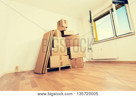cardboard boxes in an empty apartment. moving to a new apartment Hand Truck. Toned photo