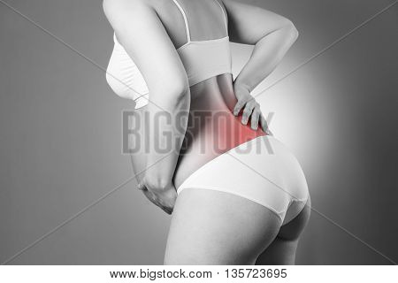 Caucasian pregnant woman in white lingerie with back pain on gray studio background. Pregnancy concept