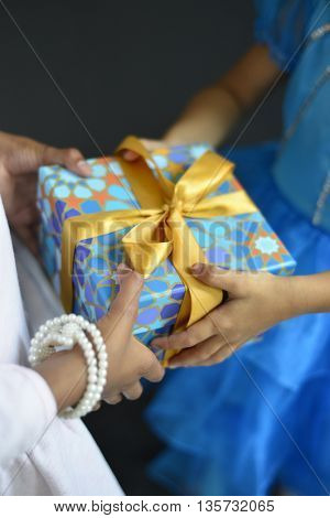 Two young girls sharing a gift. Eid and Islamic festival celebration.