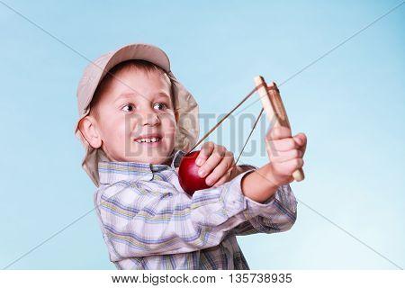 Young Boy Use Sling Shot Shoot Apple.
