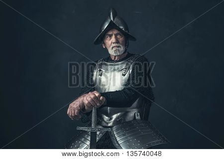 Knight With Beard In Armor Leaning On Sword.