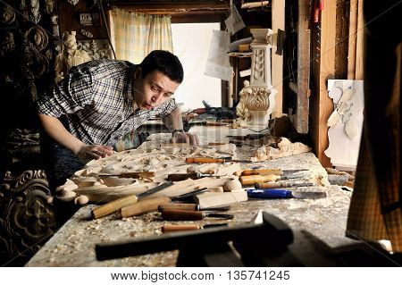 Carver in workshop of wood carving blow off sawdust